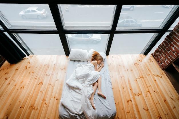 Magro descalça bonita jovem deitada na cama branca com cobertor e travesseiros e dormir.