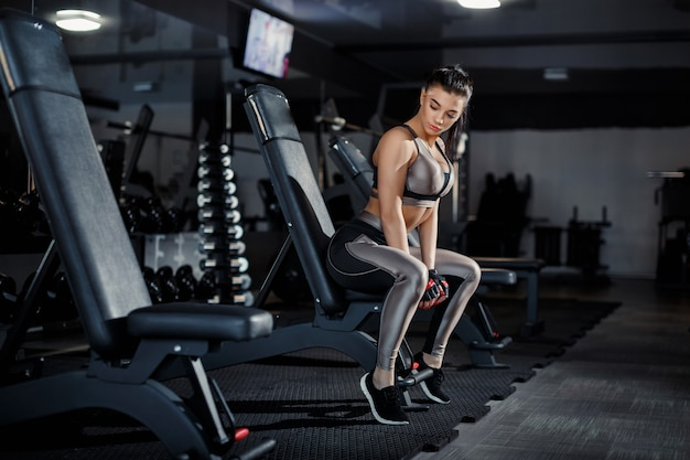 Magro, garota fisiculturista, levanta halteres pesados em pé na frente do espelho enquanto treinava no ginásio. conceito de esportes, queima de gordura e um estilo de vida saudável