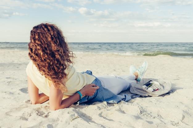 Magro morena com cabelo encaracolado brilhante espesso deitado na praia à luz do sol e olhando para o horizonte