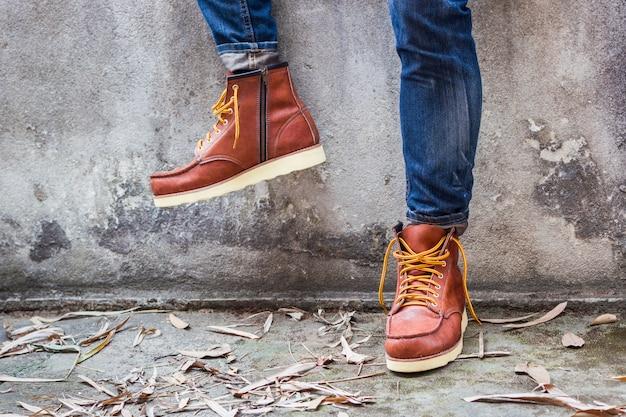 Maie pé com sapatos de couro marrom e jeans