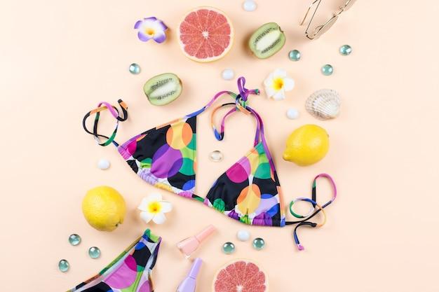 Maiô de biquíni com chapéu de palha, flores e frutas, design plano, conceito de verão. destino de praia, moda verão