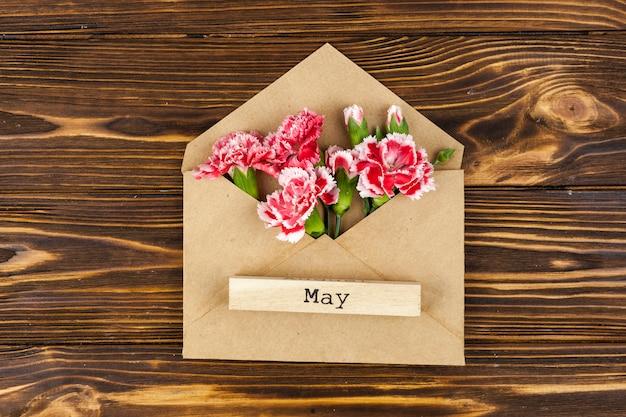 Maio texto sobre bloco de madeira no envelope com flores vermelhas de cravo