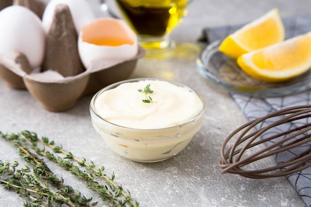 Maionese caseiro fresca do molho branco e ovos dos ingredientes, azeite do limão no fundo de pedra.