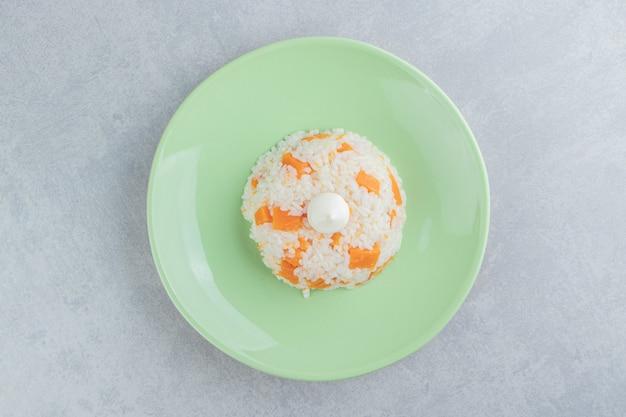Maionese no arroz no prato, no fundo de mármore.