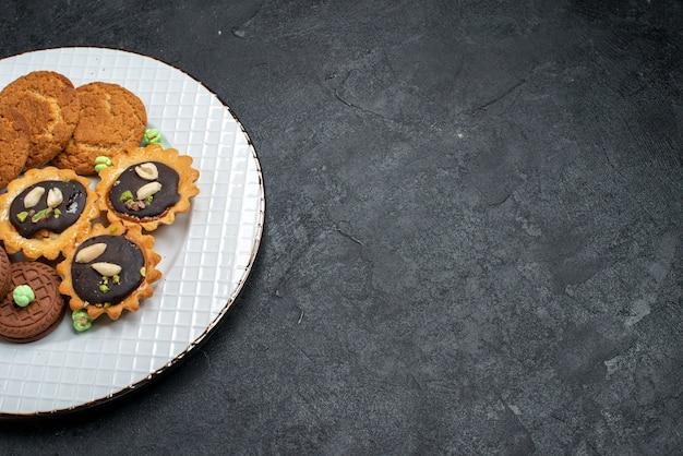 Mais de perto, de cima para baixo, diferentes cookies, biscoitos doces e deliciosos na superfície cinza.