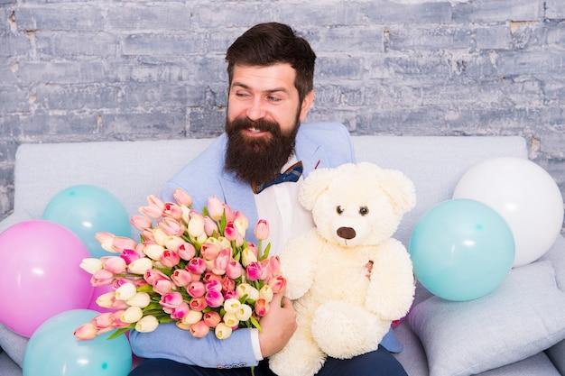 Mais do que palavras. dia da mulher. buquê de flores para 8 de março. buquê de amor. feriado internacional. feliz homem barbudo com buquê de tulipa, urso. presente de primavera. hipster de homem barbudo com buquê de flores.