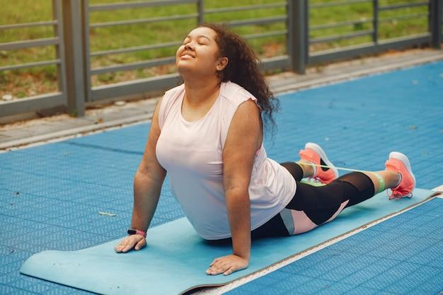 Mais do tamanho de uma mulher fazendo exercícios de alongamento