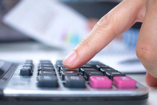 Mais perto até as mãos das mulheres estão usando uma calculadora em uma mesa. vista lateral.