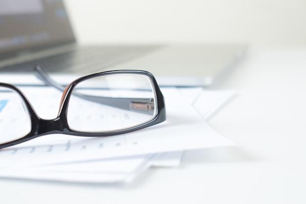 Mais perto dos óculos dos homens de negócios na carta financeira em uma mesa branca moderna.