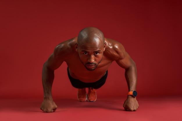 Mais saudável e forte, um homem africano forte em roupas esportivas fazendo flexões isoladas