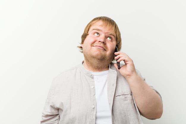 Mais tamanho homem telefonando sorrindo confiante com braços cruzados.