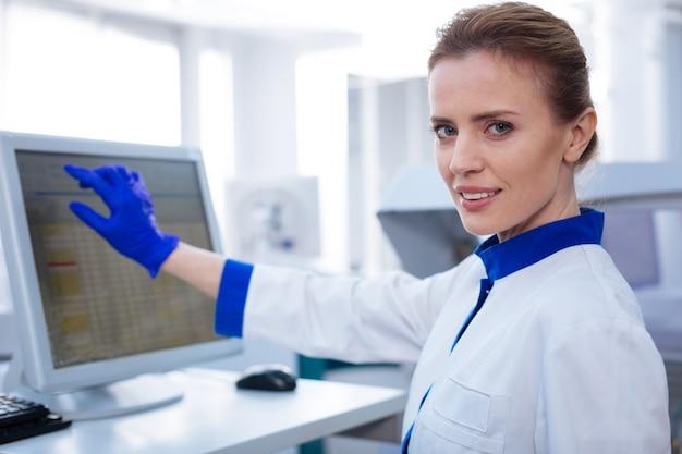 Mais um passo. retrato de uma cientista transferindo dados do experimento olhando em linha reta enquanto segura a mão perto da tela