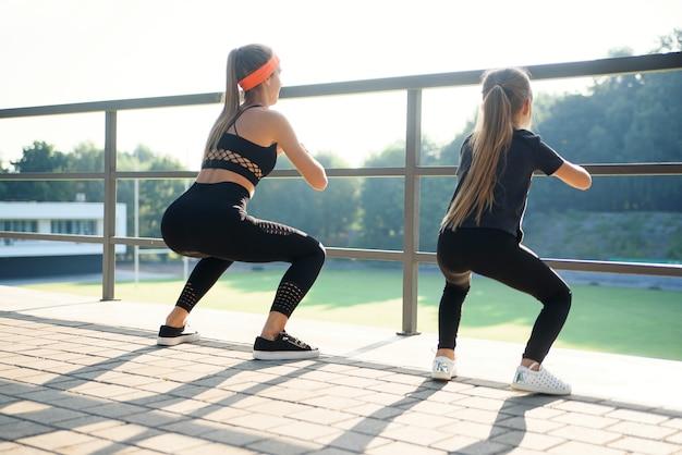 Mais velhos bonitas desportivas e irmãs mais novas que squating junto durante o treinamento da aptidão fora.