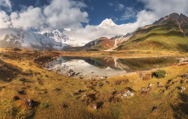 Majestosas montanhas com pedras altas e lago ao pôr do sol