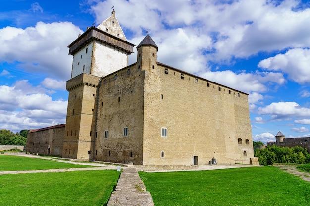Majestoso castelo medieval em narva, estônia em dia ensolarado e céu com nuvens.