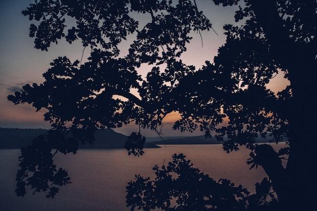 Majestoso pôr do sol na paisagem de montanhas ao longo de um lago calmo.