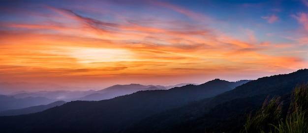 Majestoso pôr do sol na paisagem de montanhas azuis