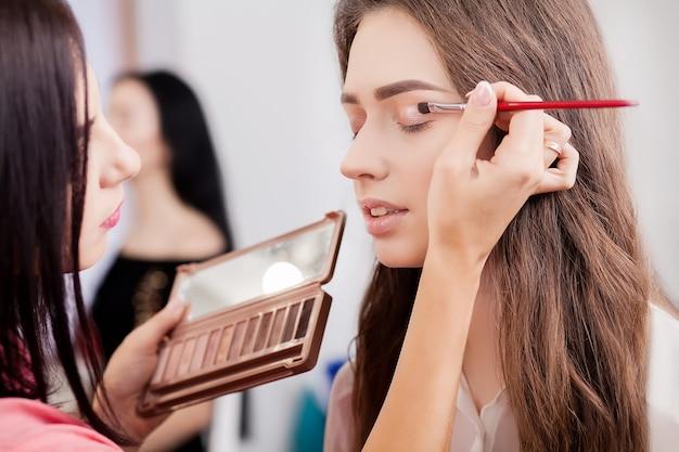 Make-up artist faz maquiagem para uma linda garota em um salão de beleza
