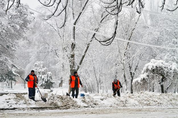 Makeevka, ucrânia - 6 de fevereiro de 2020: trabalhadores de serviços comunitários de uniforme com pás removem a neve após uma queda de neve. colapso do tempo. editorial