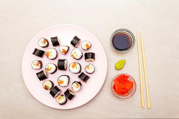 Maki rola com gengibre, wasabi e molho de soja no prato rosado
