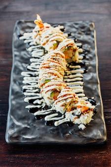 Maki sushi com arroz, tempura de camarão, abacate e queijo no interior coberto de farinha de tempura crocante. cobertura com molho teriyaki e maionese.