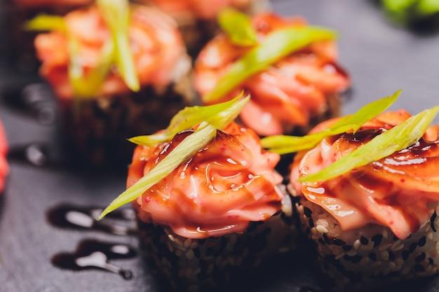 Maki sushi rolls com salmão na pedra preta sobre fundo escuro. com gengibre e wasabi. menu de sushi. comida japonesa. closeup de deliciosa comida japonesa com rolo de sushi. foto horizontal.