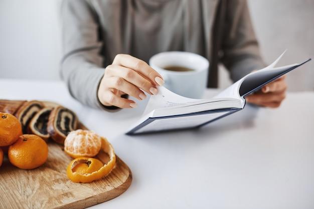 Mal posso esperar para ler o livro inteiro. menina está apaixonada por história escrita em páginas de romance, almoçando, bebendo chá com tangerinas e bolo enrolado. trabalhador de escritório descansando após reunião com clientes