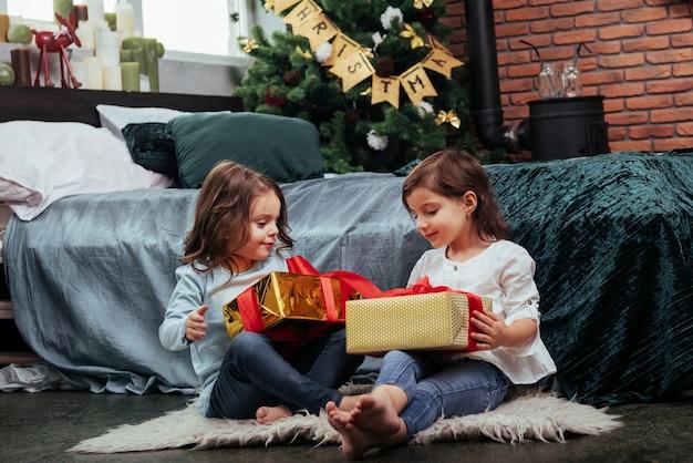 Mal posso esperar para ver o que tem dentro. férias de natal com presentes para essas duas crianças que estão sentadas dentro de casa no belo quarto perto da cama.