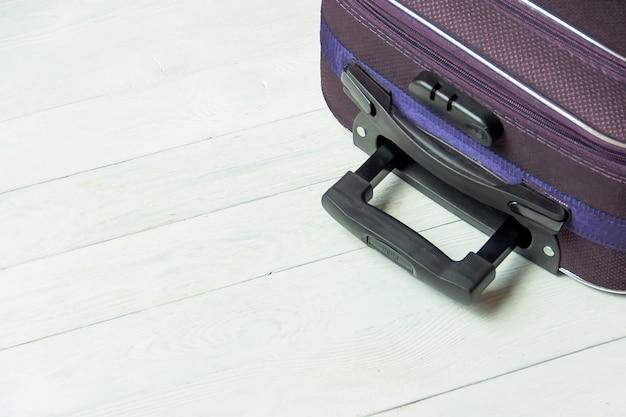 Mala aberta com acessórios de viagem na mesa de madeira branca com copyspace.