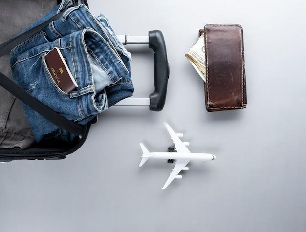 Mala aberta, feita para viajar com o passaporte da tailândia em fundo cinza
