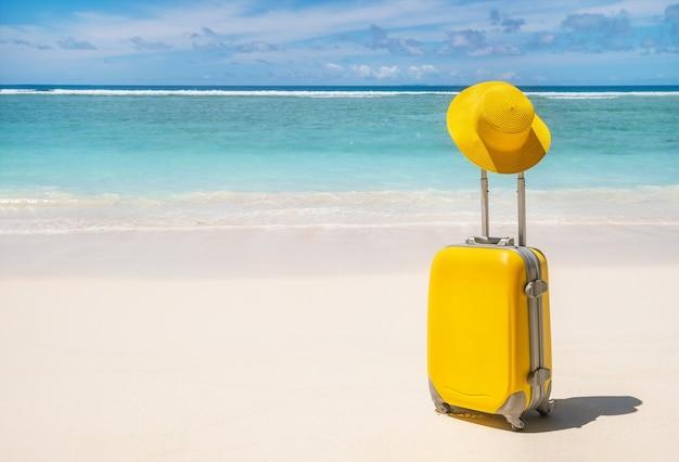 Mala amarela com chapéu amarelo em uma praia tropical vazia com água turquesa