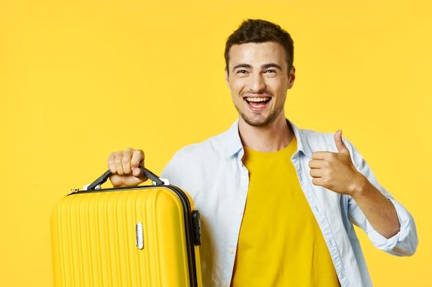 Mala amarela de homem alegre no estilo de vida de viagens de férias