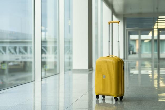 Mala amarela solitária no terminal do aeroporto