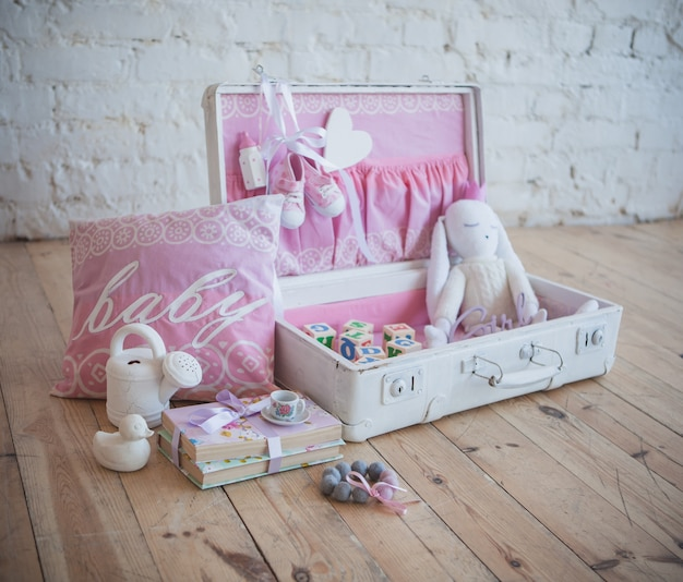 Mala branca e rosa com brinquedos no fundo de madeira e parede de tijolos