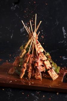 Mala churrasco grelhado (churrasco) com pimenta sichuan, com temperos caindo mala em pó e pimenta, comida de rua quente e picante e deliciosa.