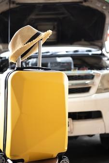 Mala com chapéu e carro, preparar ou verificar o seu carro antes de um conceito de viagens rodoviárias