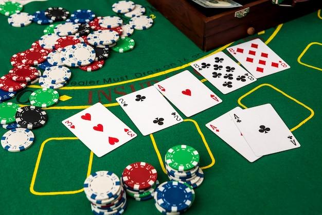 Mala com dólares, cartas de jogar, fichas de pôquer na mesa de pôquer verde.