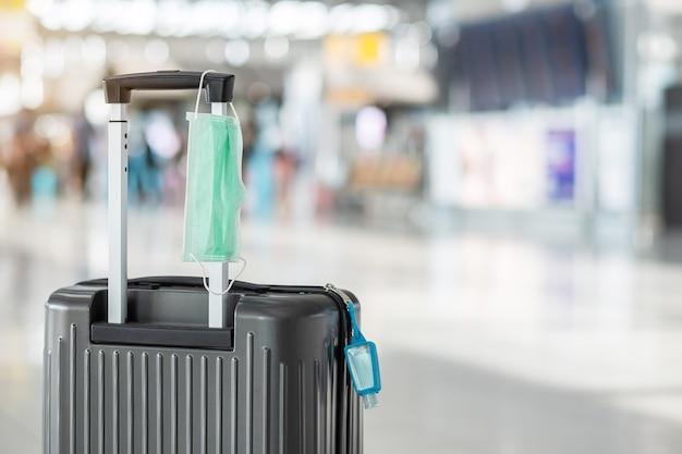 Mala de bagagem com máscara cirúrgica e desinfetante para as mãos com álcool gel no terminal do aeroporto internacional