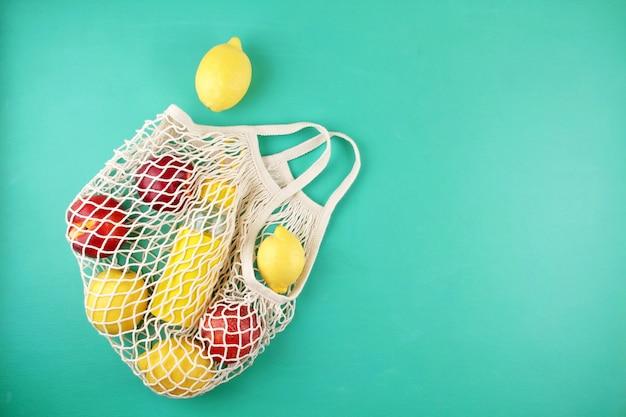 Mala de compras reutilizável com limões, frutas e garrafa de vidro