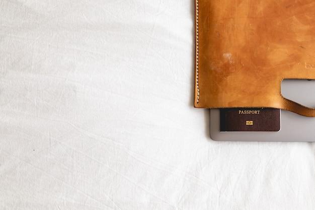 Mala de couro com passaporte e laptop no conceito de viagens de negócios.