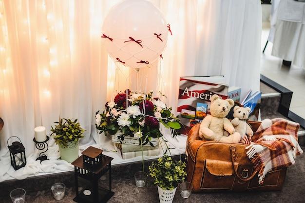 Mala de couro velha, ursinhos de pelúcia, livros e flores