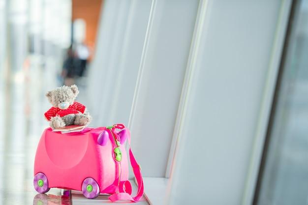 Mala de crianças pequenas com urso de brinquedo no aeroporto internacional perto da janela