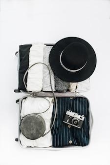 Mala de mão com roupas femininas elegantes e conceito de viagens