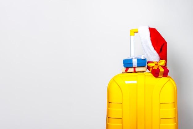 Mala de plástico amarela com chapéu de papai noel vermelho
