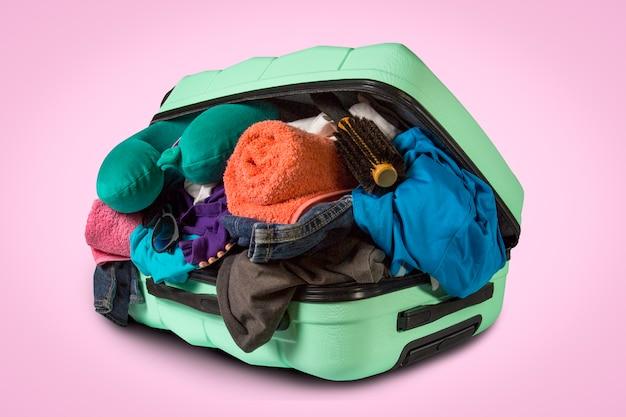 Mala de plástico com rodas, transbordando coisas sobre uma superfície rosa. conceito de viagens, viagem de férias, visita a parentes