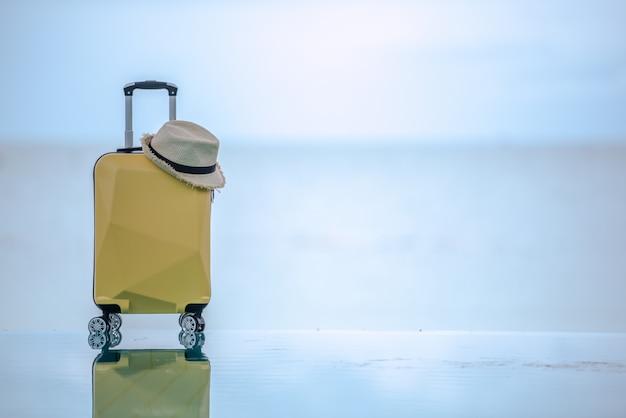 Mala de viagem amarela com chapéu na praia.