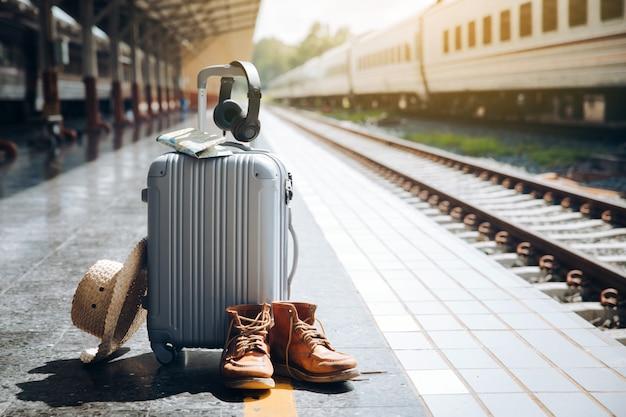 Mala de viagem, chapéu de palha, mapa, fone de ouvido e botas de sapato no tra