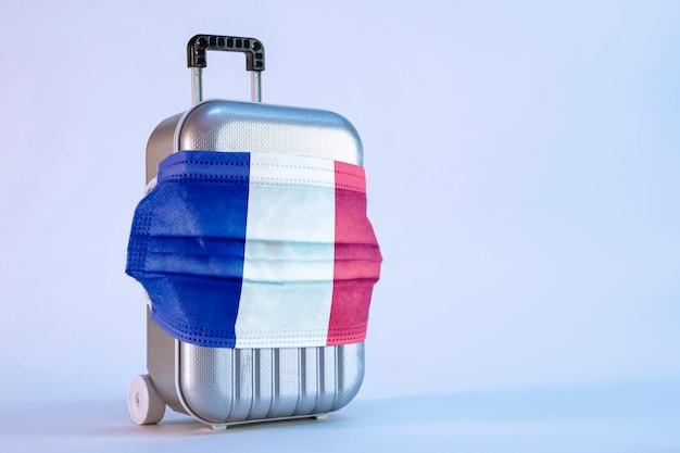 Mala de viagem com máscara médica e bandeira da frança sobre fundo branco