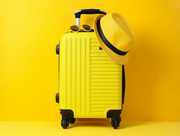 Mala de viagem com óculos escuros e chapéu amarelo