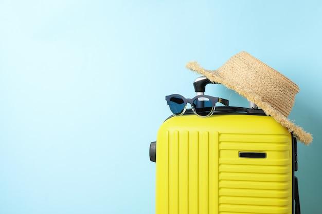 Mala de viagem com óculos escuros e chapéu azul